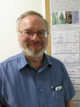 Dr. Chris Schardl standing by the endophyte poster.